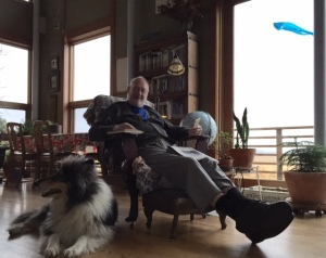 Steve Shoemaker in his favorite chair with Blazer, his collie by his side, his iPhone, book, and newspaper. Kite soaring outside the window