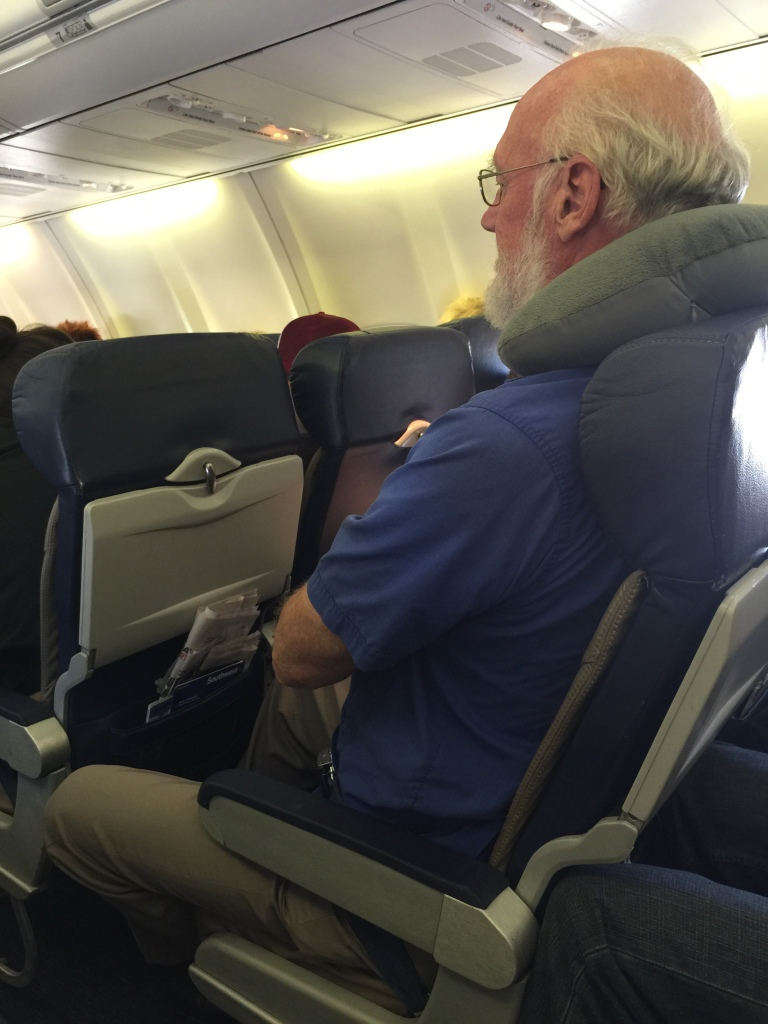 "photo of 6'8"" poet Steve Shoemaker crammed into seat of an airplane."