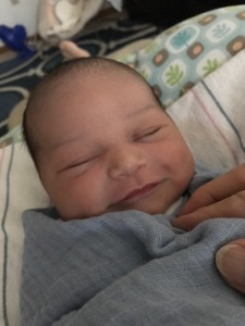 Elijah smiling in swaddle