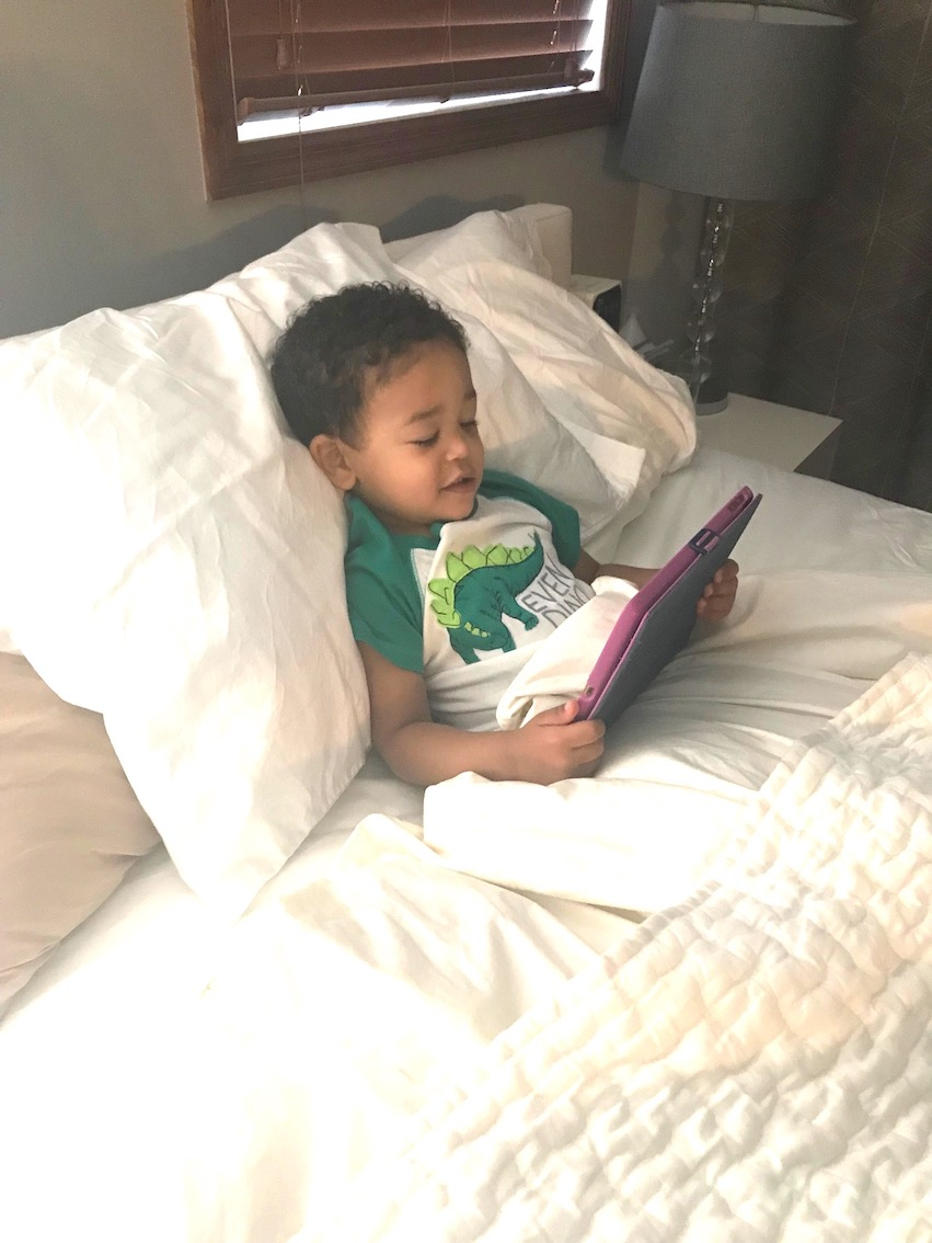 Photo of Elijah in bed watching the story of The Three Little Wolves and the Big Bad Pig on an iPad.